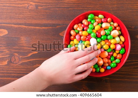 Hand takes candy - stock photo