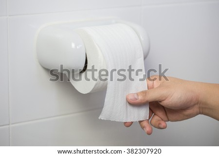 Hand taking a new tissue roll on toilet paper hanging - stock photo