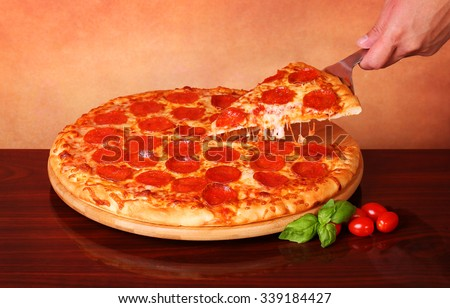 Hand taking a slice of Pepperoni Pizza