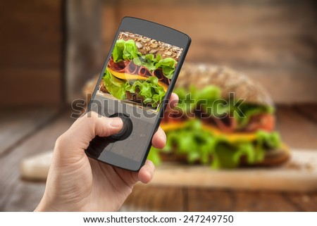 Hand taking photo of sandwich with smatphone on the wooden table with slices of tomatoes, ham, cheese and lettuce - stock photo