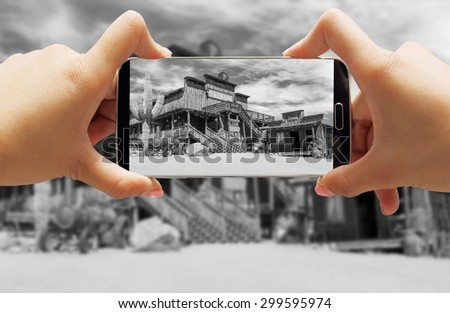Hand taking photo with smartphone of Wild west cowboy town in black and whitein arizona - stock photo