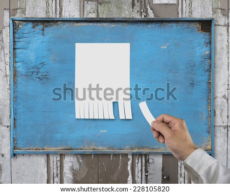 hand tear paper from blank advertising posted on wooden billboard and marked with your own message - stock photo