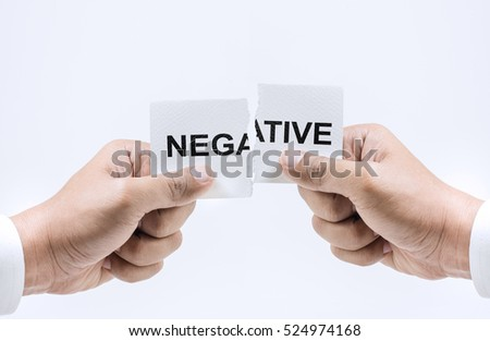 Hand tearing paper with Negative word.For business success concepts.Self belief motivation.Concepts of overcoming challenges and positive attitude thinking.