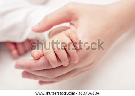 Hand the sleeping baby in the hand of mother close-up (Soft focus and blurry)