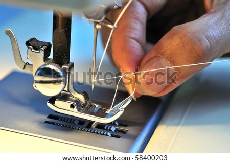 Hand threading needle into sewing needle. For concepts such as fashion and design, work and industrial.