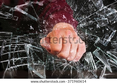 Hand through a broken glass window. - stock photo