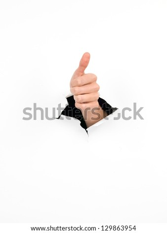 hand through a hole in a white paper with thumb up gesture, isolated - stock photo