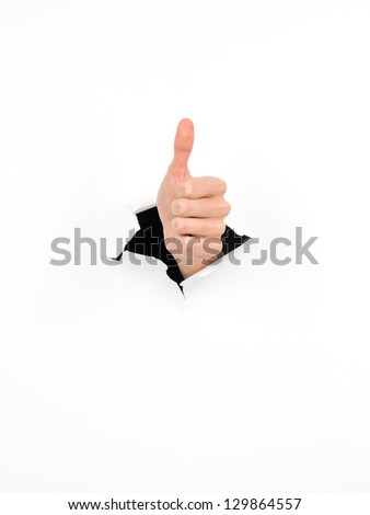 hand through a hole in a white paper with thumb up gesture, isolated