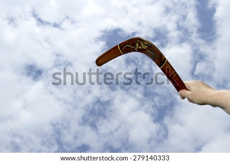 Hand throwing a painted wooden boomerang with blue sky and cloud background.