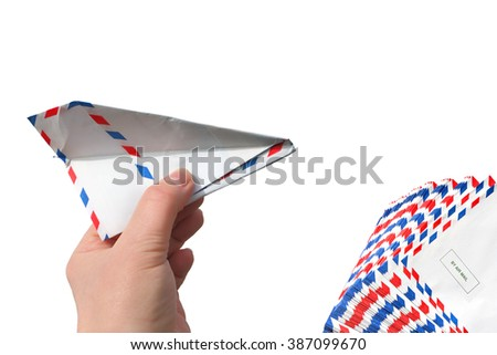 Hand throwing  a paper plane (made of Post envelope) and pile (pack) of post envelopes. Isolated on a white background.  - stock photo