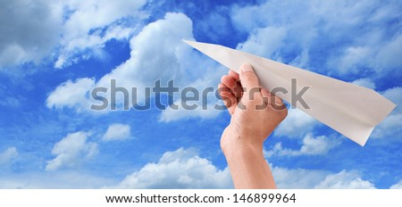 hand throwing paper plane to blue sky  - stock photo