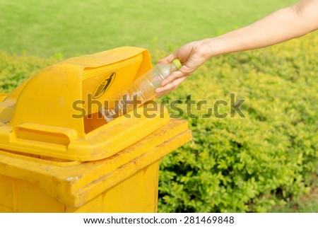 Hand throwing plastic water bottle in recycle bin - stock photo