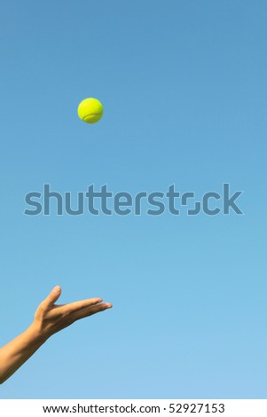 Hand-thrown tennis in the blue sky background - stock photo