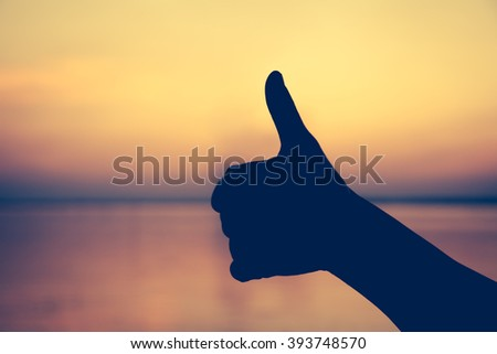 Hand thumb up on colorful sunset sky background. Gesture of the hand. Symbol is mean to good, yes, like. Achievement concept. - stock photo