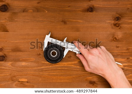hand tools in the hands on a wooden background