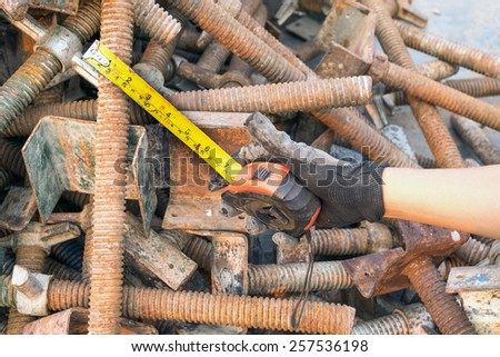 Hand Tools Measuring tape with steel bolts, nuts, screws scaffolding pole. - stock photo