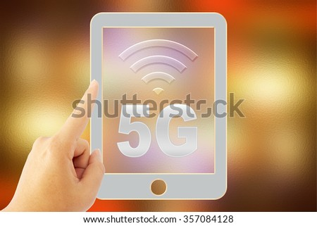 """hand touch tablet """"5G"""" over blurred background - stock photo"""