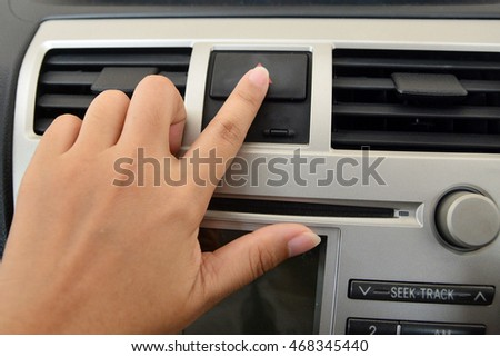Hand touching emergency button in car