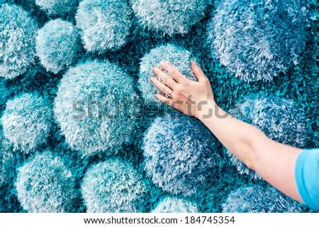 Hand touching fluffy blue carpet with stone like decoration - stock photo