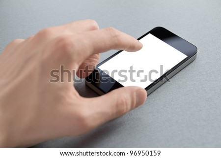 Hand touching mobile smart phone with blank screen. Isolated on white. - stock photo