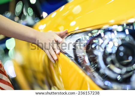 Hand touching on car's surface - stock photo