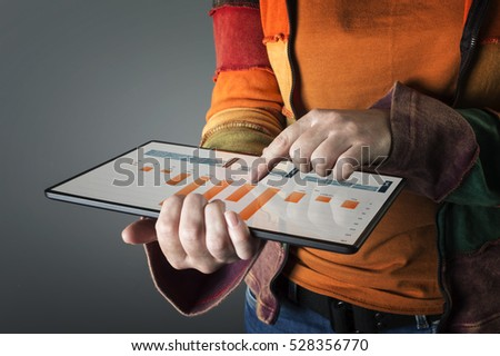 Hand touching screen modern tablet with financial graph. Business analysis concept