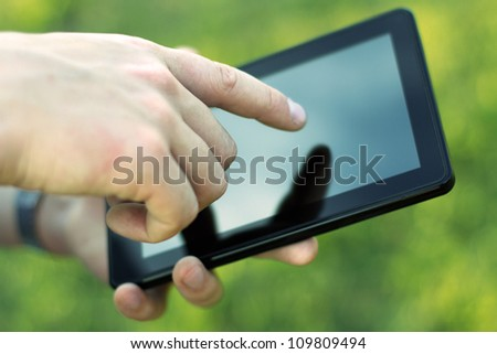 Hand touching screen on modern digital tablet pc. Close-up image
