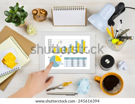 Hand touching tablet screen with chart over office desk background - stock photo