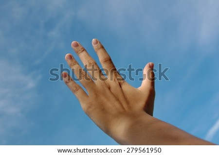 hand touching the blue sky - stock photo