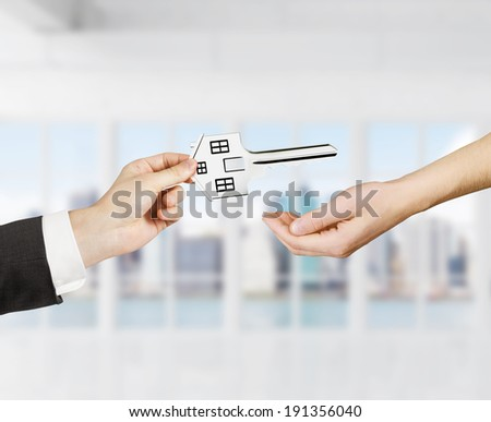 hand transfers the house shaped key - stock photo