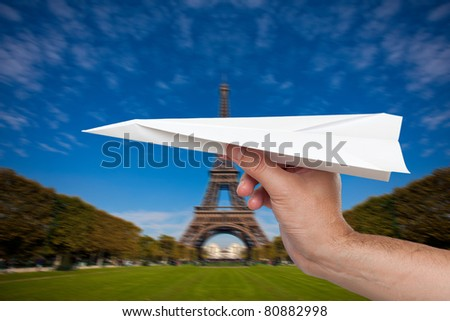 Hand trowing a paper plane in Paris - stock photo