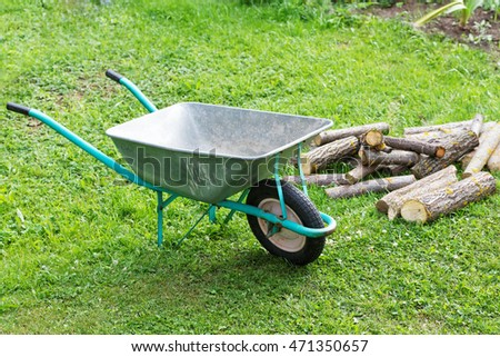 hand truck with firewood on the green grass