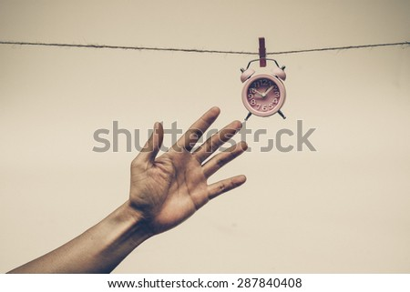 Hand trying to catch a clock hung on a rope - time waits for no man concept - stock photo