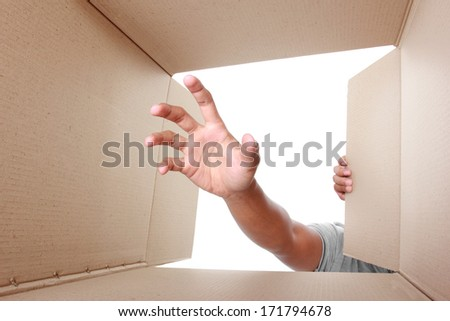 hand trying to grab something inside box - stock photo