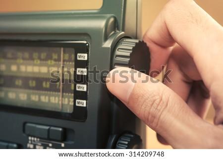 Hand tuning radio button - stock photo