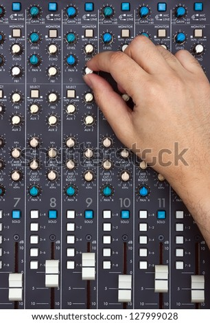 Hand turning knob on a mixing desk - stock photo
