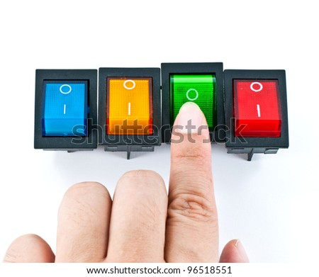 Hand turning on a green electrical switch - stock photo