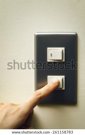 hand turning on the light with a wall switch