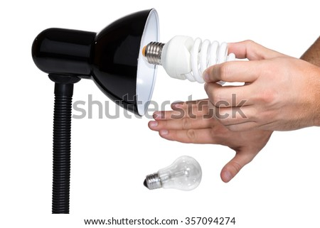 Hand twists saving bulb in black lighting abandoning incandescent lamps isolated on a white background - stock photo