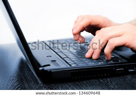 Hand typing laptop on desk - stock photo