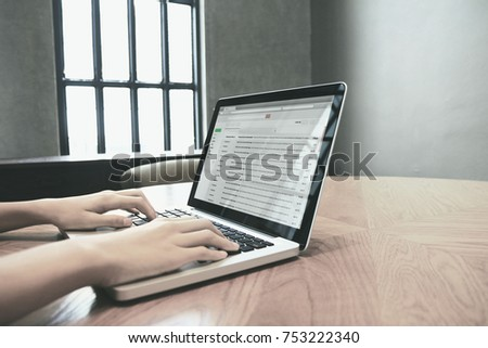 Hand typing message to send email on computer laptop.
