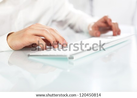 hand  typing on a white keyboard