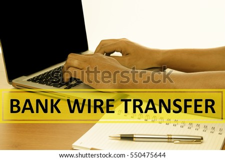 Hand Typing on keyboard with text BANK WIRE TRANSFER