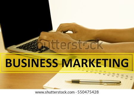 Hand Typing on keyboard with text BUSINESS MARKETING