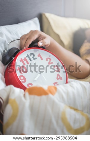 Hand under blanket reaching out for alarm clock in bedroom with men sleeping - stock photo