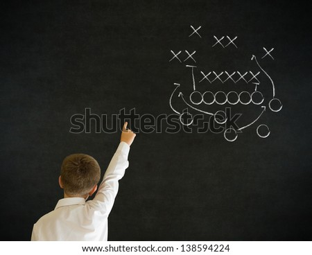 Hand up answer boy dressed up as business man with chalk American football strategy on blackboard background - stock photo