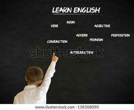 Hand up answer boy dressed up as business man with learn English on blackboard background - stock photo