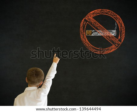 Hand up answer boy dressed up as business man with no smoking chalk sign on blackboard background - stock photo