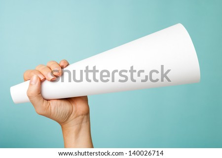 Hand up holding a white blank megaphone on blue background. - stock photo