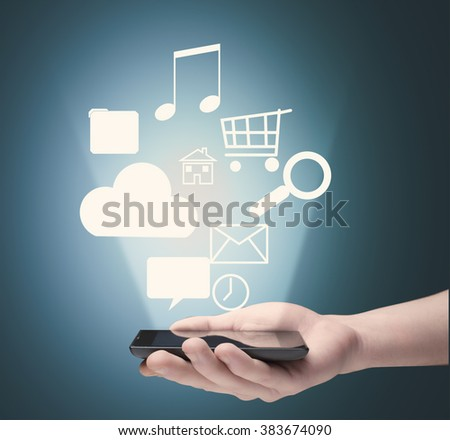 Hand use a smart phone and hologram of different icons rising up  - stock photo